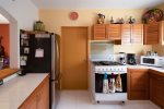 Fully-equipped kitchen with attached laundry room with washer and dryer.