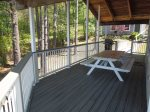Covered deck has picnic table and chairs