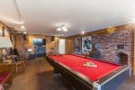 The lower level includes the pool and game room with TV