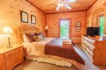 Basement Bedroom 4 Features a Queen Size Bed, Flat Screen Tv, & Access to Patio