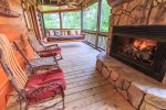 Screened In Deck off Living Room Features a Gas Fireplace, Dining Table for 6, Ample Seating, and Swing