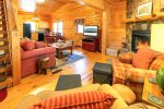 Living Room Features a Flat Screen TV, Wood Burning Fireplace, & Access to Covered Screened in Deck