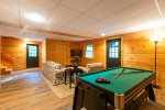 Basement Level Entertainment Area Features Sitting Area, Flat Screen TV, and Pool Table/ Air Hockey Table Combo