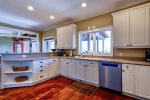 Fully Equipped Kitchen Features Gas Range, Double Ovens, and Bar Seating for 3