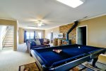 Basment Level Living Room Features a Wood Burning Fireplace, 40 4K Smart TV, Ample Seating, Pool Table, and Air Hockey