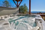 Covered Deck off Basement Features Large 7 Person Hot Tub, Rocking Chairs, Hammock, and Breathtaking Mountain Views