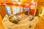 Basement Living Room Features a Large Sectional, Flat Screen Tv, & Access To Patio