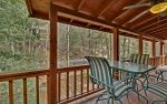 Main Level Covered Deck Features 2 Rocking Chairs and a Dining Table