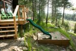 Outdoor play area with slide and sandbox
