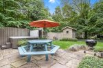 Amazing backyard patio space with hot tub, outdoor shower, picnic table, and BBQ grill