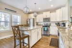 The spacious eat-in kitchen island has seating for 5 guests.