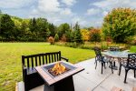 The back patio of the Aster Pointe Cottage includes a gas fire-pit, BBQ grill, patio furniture set, and picnic table.
