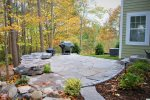 The spacious river-front backyard features a gorgeous stone patio and wall, with gas BBQ grill and waterfall.