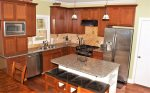 The fully equipped kitchen features a built-in wet bar and dine-in island with granite counter-tops.