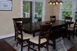 The formal dining room has 6 chairs and 2 large benches, with sliding patio doors to the screened in dining porch.