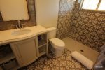 Bathroom with walk in shower that includes rain shower and handheld fixtures