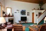 The living room has a gas fireplace and flatscreen TV, perfect for relaxing after a day on the mountain