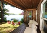 Covered porch with outdoor seating and lake in the background