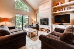 Bright living room with vaulted ceilings, wood fireplace and smart TV