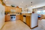 Kitchen with full-size refrigerator, oven, microwave, dishwasher and small appliances