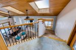 The landing to the second level overlooks the main level living room and to the right is the door to the private deck with brand new hot tub. The main living space also has multiple sky lights and two large ceiling fans
