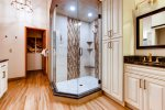 Full en-suite master bath is accented with glass tile and has granite vanity