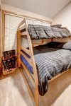 Captain bunk beds with a twin bed on top and a double bed on the bottom. Located behind the curtain off the dining room.