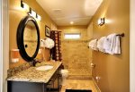 Jack and Jill bathroom with large tumbled marble shower with Tommy Bahama amenities