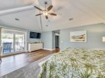 Master Bedroom with Mounted TV and Private Deck Overlooking Pool at 29 Pelican