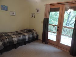 Single bed in the 3rd bedroom with French doors leading to the back deck