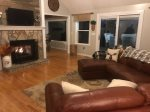Large open living room with a Gas Fireplace and Sectional Couch, Leads to Screened in Porch.