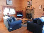 The living area is open with a comfortable sofa, love seat ,TV and gas fireplace.