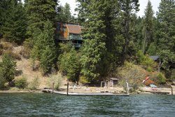 Large waterfront home with expansive lake views, surrounded by huge pine trees and nestled along the shores of Lake coeur d`Alene