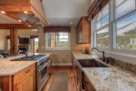 Well equipped gourmet kitchen with granite, stainless steel appliances, and plenty of space.
