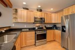 Large open kitchen with stainless appliances, granite counters, and cooking utensils.