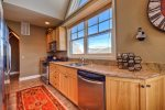 Large open kitchen with granite counters, stainless steel appliances and views.