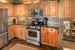 Fabulous open kitchen with stainless steel appliances and all cooking supplies.