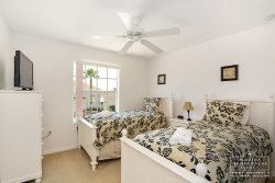 The fifth bedroom has 2 twin beds, a flatscreen TV, nightstands and ample closet space.