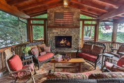 Outdoor screened-in porch with rock fireplace