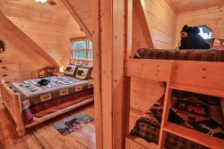 Upstairs queen bed in loft with bunk beds for the kids