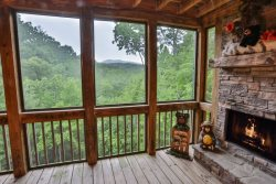 Screened in porch with gas fireplace overlooking mountains.
