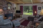 A propane fireplace sets the mood for relaxation in the very comfortable living room of the White Fir Cottage.