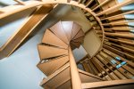 Spiral staircase leads to upper master loft and down to lower sleeping room.