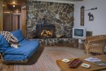 Living room of the Homestead has a floor to ceiling stone fireplace and views of the Wallowa Mountains.