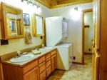 Main floor bathroom with shower/tub combo, washer and dryer and double vanities.