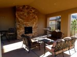 Covered poolside patio lounge with fireplace and comfortable patio furniture