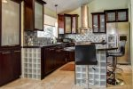 Gourmet chef kitchen with high-end appliances and large bar