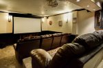 Custom movie theater room with retractable screen and recliner seating