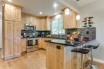Beautiful deluxe kitchen with wood floor, deluxe stainless steel appliances, and custom granite counters