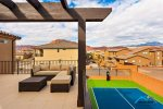 Private sports court with a pickleball net and basket ball hoops, upper level balcony